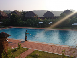 a man cleaning a big swimming pool